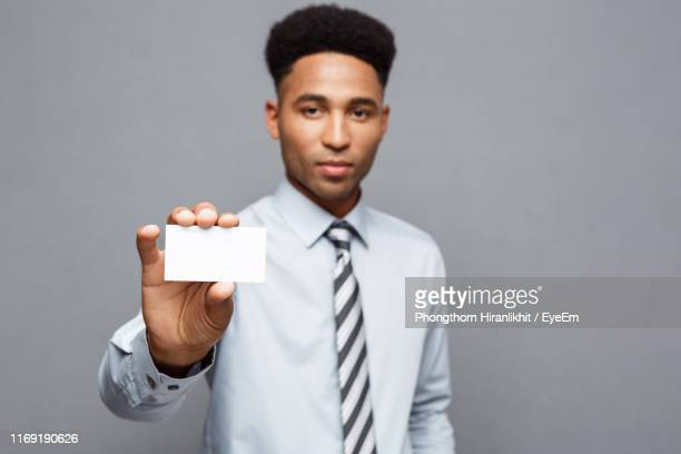portrait of businessman holding blank business card against gray background - グリーティングカード ストックフォトと画像