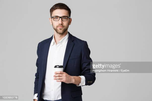 portrait of businessman holding disposable cup while standing against gray background - スーツ ストックフォトと画像