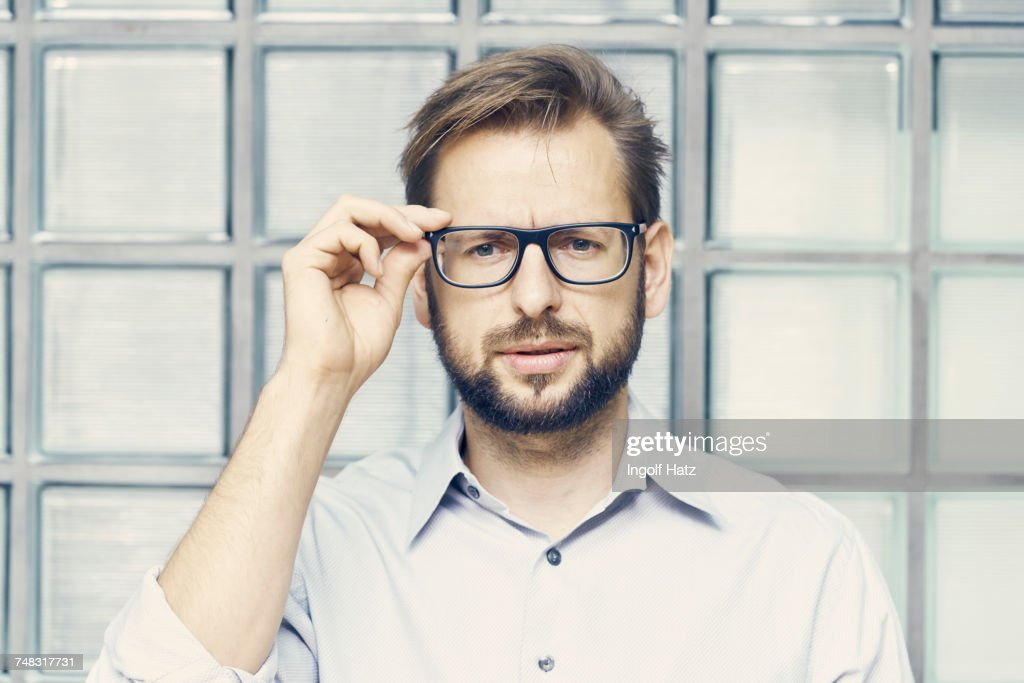 Portrait of businessman holding eyeglasses by office glass wall : Stock Photo