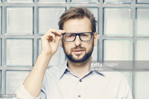 Portrait of businessman holding eyeglasses by office glass wall