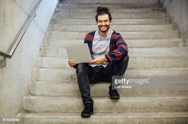 portrait of businessman holding laptop while sitting on steps - man bun stock pictures, royalty-free photos & images