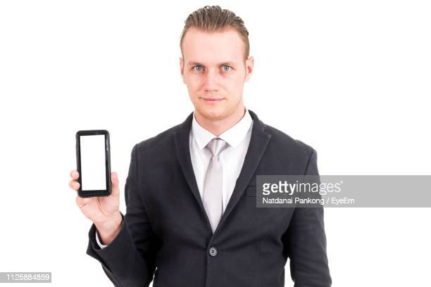 Portrait Of Businessman Holding Mobile Phone Against White Background