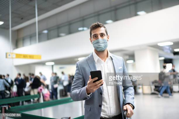 portrait of businessman holding mobile phone at airport using protective mask - airport stock pictures, royalty-free photos & images