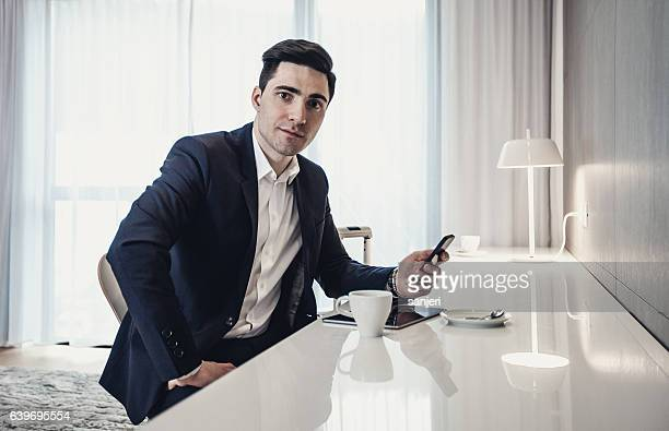Portrait of Businessman in a Hotel Room Beside a Desk