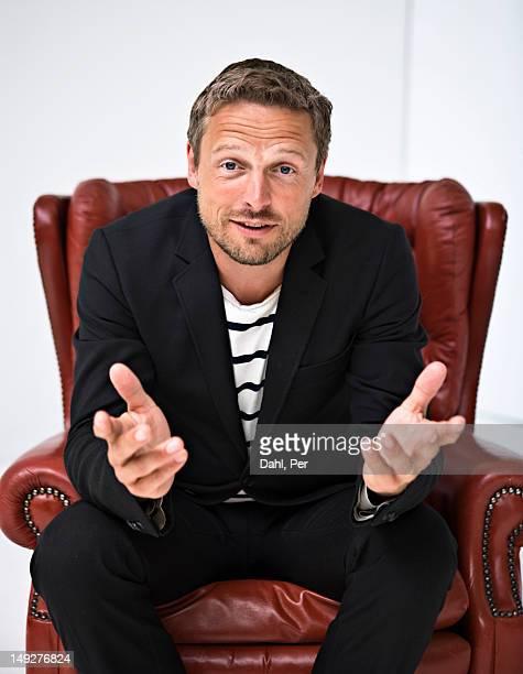 portrait of businessman in armchair - armstoel stockfoto's en -beelden