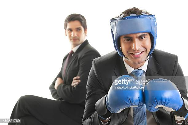 Portrait of businessman in boxing gloves and head protector with colleague sitting over white background