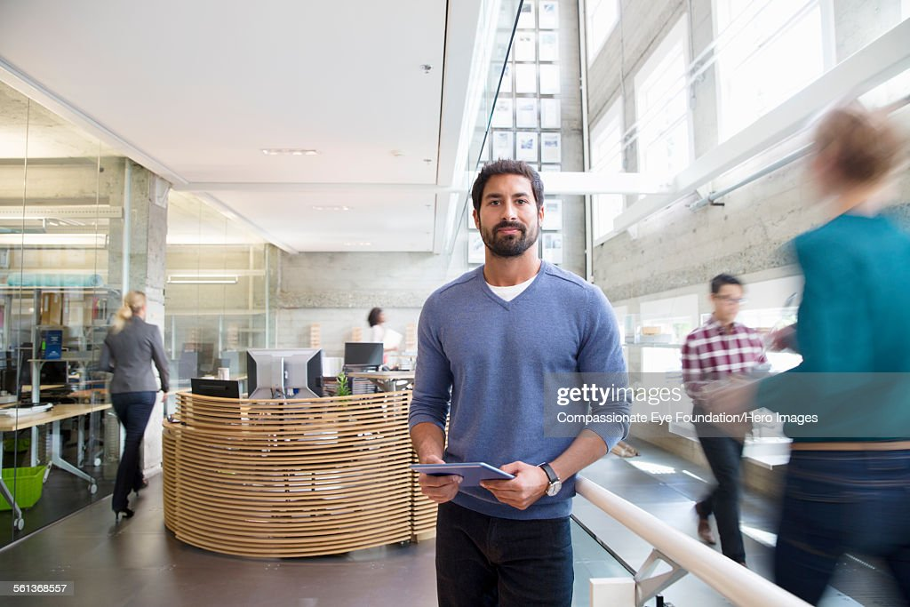 Portrait of businessman in busy lobby : Stock Photo