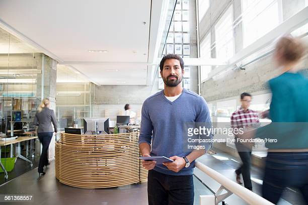 Portrait of businessman in busy lobby