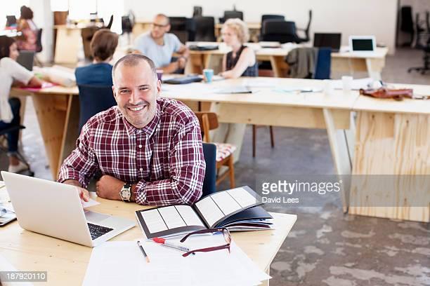Portrait of businessman in busy modern office