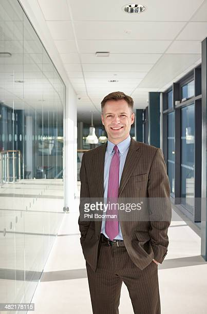 portrait of businessman in corridor - brown suit stock photos and pictures