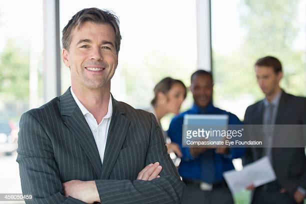 Portrait of businessman in office with coworkers