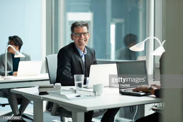 portrait of businessman in open office - incidental people stock pictures, royalty-free photos & images