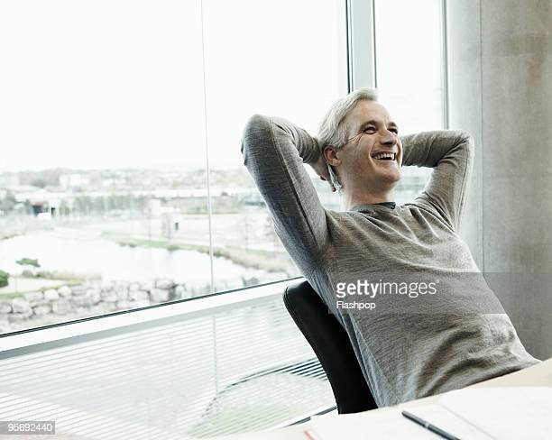 portrait of businessman laughing - zurücklehnen stock-fotos und bilder