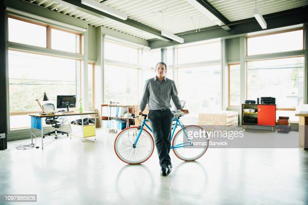 portrait of businessman leaning against bike in creative studio - studio workplace stock pictures, royalty-free photos & images