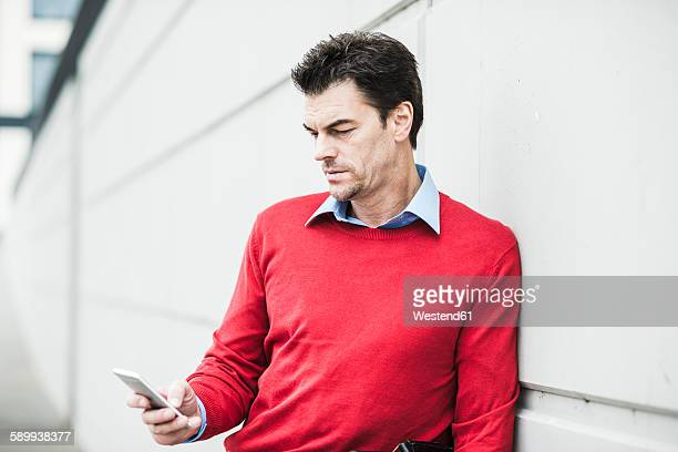 Portrait of businessman leaning against concrete wall looking at his smartphone