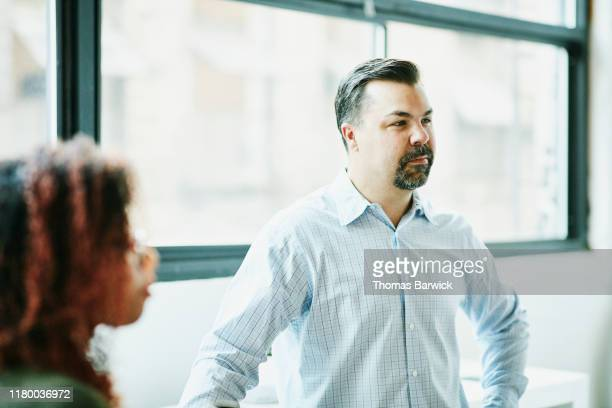portrait of businessman listening during meeting with colleagues in office - goatee stock pictures, royalty-free photos & images