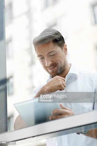 Portrait of businessman looking at digital tablet