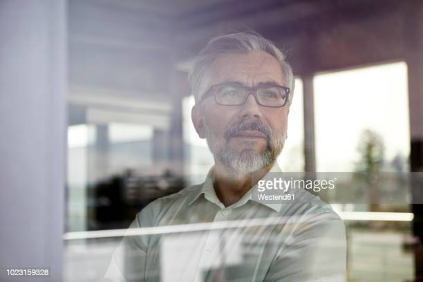 portrait of businessman looking out of window - respekt stock-fotos und bilder