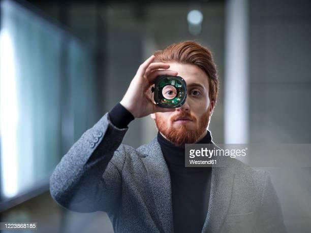 portrait of businessman looking through an object in modern office - futuristisch stock-fotos und bilder