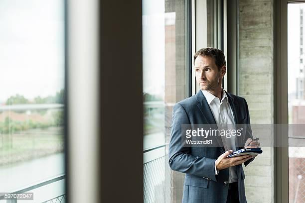 Portrait of businessman looking through window