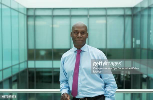 Portrait of businessman on atrium balcony