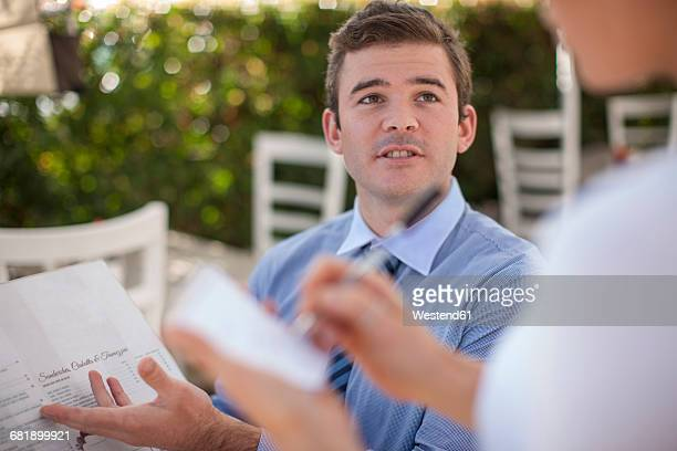 Portrait of businessman ordering at outside restaurant
