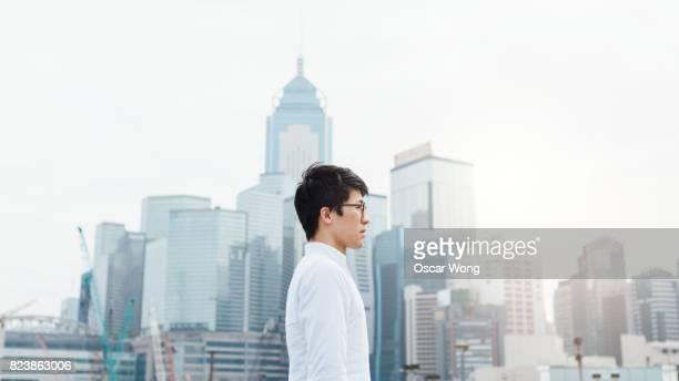 Portrait of businessman, outdoors, against Hong Kong cityscape