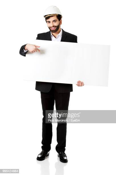 Portrait Of Businessman Pointing At Placard Against White Background