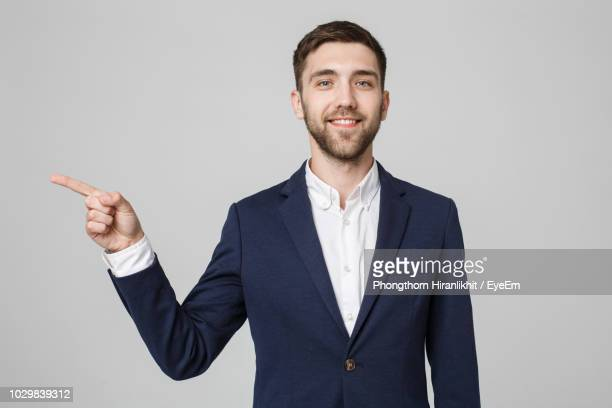 portrait of businessman pointing while standing against gray background - apontando sinal manual - fotografias e filmes do acervo