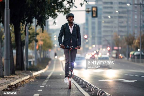 portrait of businessman riding push scooter on bicycle lane in the evening - sports helmet stock pictures, royalty-free photos & images