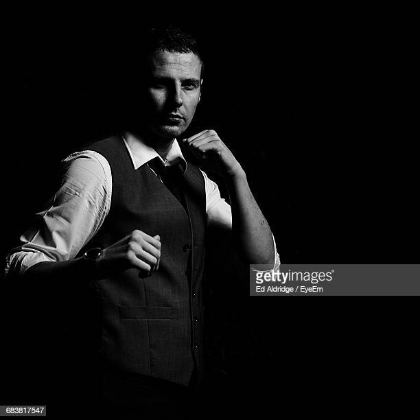 Portrait Of Businessman Shadow Boxing Against Black Background