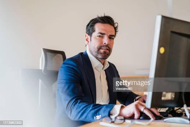 portrait of businessman sitting at desk in wooden open-plan office - facial hair stock pictures, royalty-free photos & images