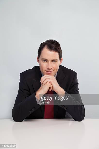 Porträt eines Geschäftsmann, sitzen am Tisch