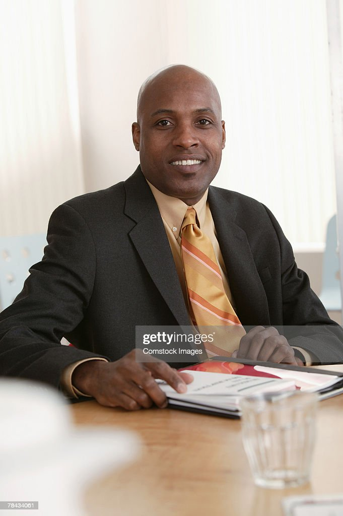 Portrait of businessman sitting at table : Stockfoto