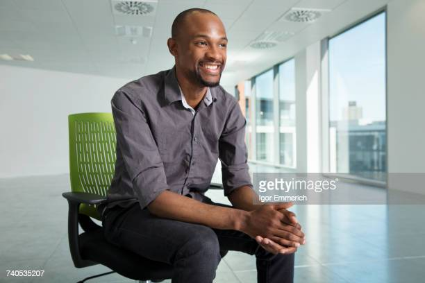 portrait of businessman, sitting in chair, in empty office space - black man bulge stock pictures, royalty-free photos & images