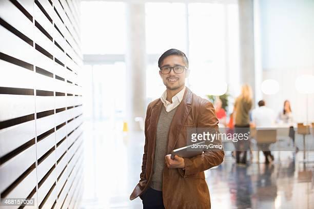 portrait of businessman smiling in office - mensen op de achtergrond stockfoto's en -beelden