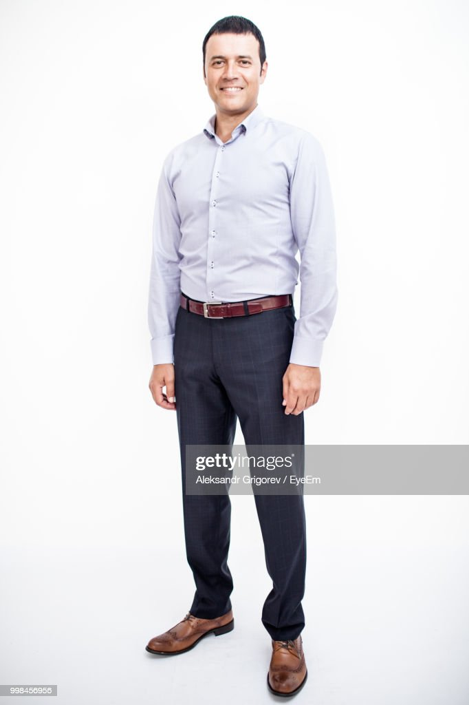 Portrait Of Businessman Smiling While Standing Against White Background : Stock Photo
