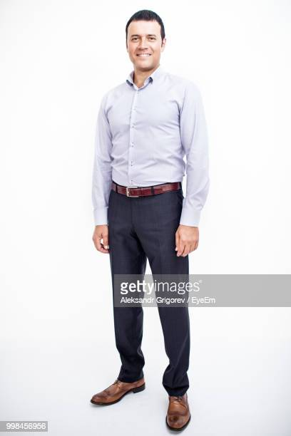 portrait of businessman smiling while standing against white background - stare in piedi foto e immagini stock