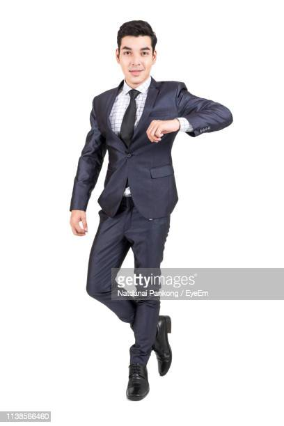 portrait of businessman standing against white background - physical position stock pictures, royalty-free photos & images