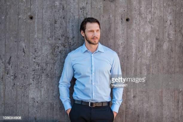 portrait of businessman standing  at concrete wall - hellblau stock-fotos und bilder