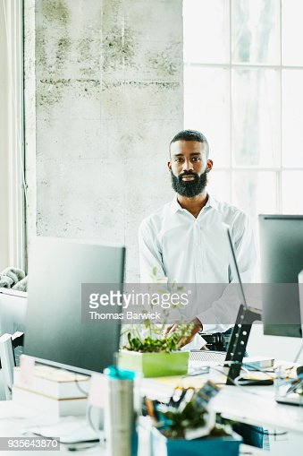 Portrait of businessman standing at workstation in high tech start up office