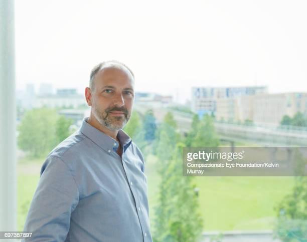 Portrait of businessman standing by office window