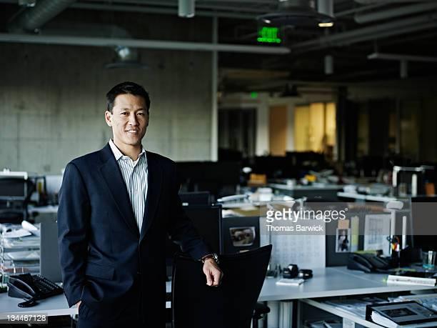 portrait of businessman standing in empty office - un seul homme d'âge moyen photos et images de collection