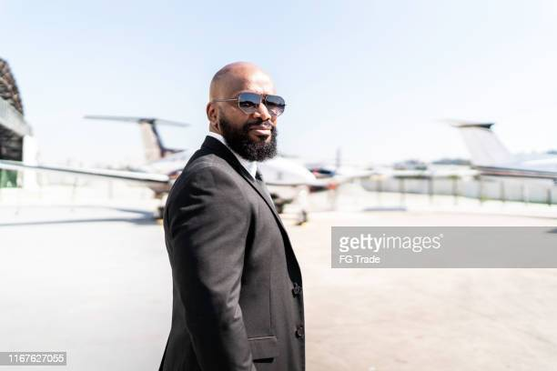 portrait of businessman standing in front of corporate jet - best sunglasses for bald men stock pictures, royalty-free photos & images
