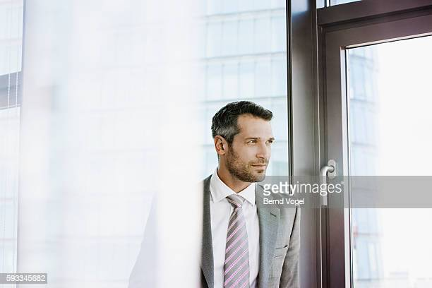 Portrait of businessman standing in office and looking through window