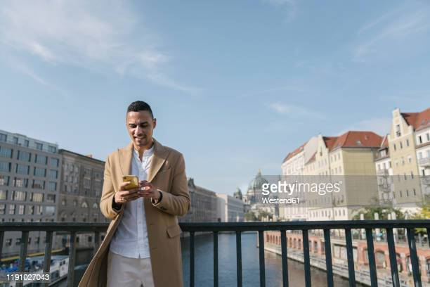 portrait of businessman standing on a bridge looking at smartphone, berlin, germany - central berlin stock pictures, royalty-free photos & images