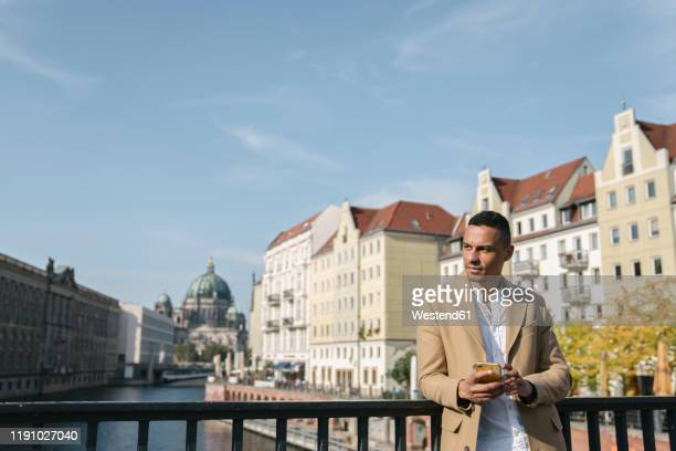 portrait of businessman standing on a bridge with smartphone looking at distance, berlin, germany - ベルリン王宮 ストックフォトと画像