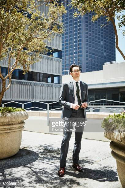 Portrait of businessman standing on deck of office building