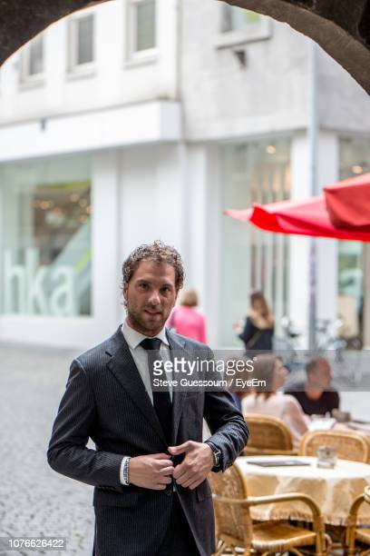 portrait of businessman standing on footpath in city - steve guessoum stockfoto's en -beelden