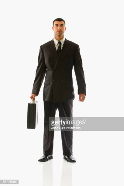Portrait of businessman standing with briefcase